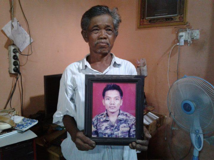 Sukarmin (60) membawa foto mendiang anaknya, Riyanto.