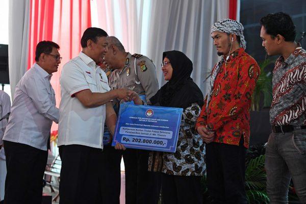 Dok. Medcom - Menko Polhukam Wiranto didampingi Ketua Lembaga Perlindungan Saksi dan Korban Abdul Haris Semendawai memberikan kompensasi secara simbolis kepada korban aksi terorisme di Kantor LPSK, Jakarta (6/9/2018).